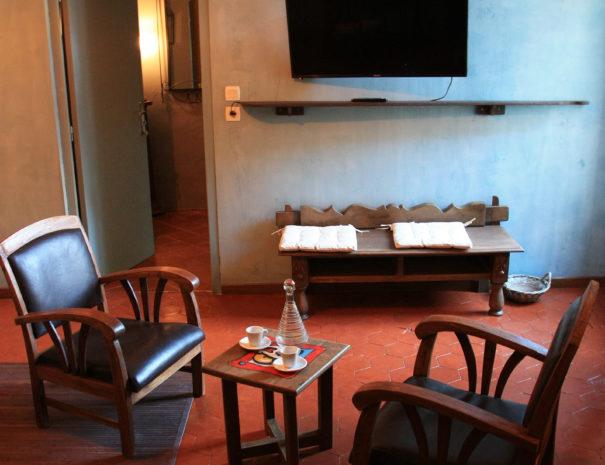 Salon avec fauteuils, table basse et TV écran plat